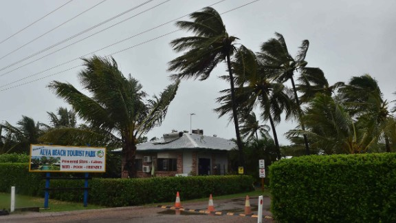 """Palm trees blow in the wind in the town of Ayr in far north Queensland as Cyclone Debbie approaches on March 28, 2017.Lashing rain and howling winds battered northeast Australia as towns went into lockdown ahead of a """"monster"""" cyclone making landfall, with thousands evacuated amid fears of damage and tidal surges. / AFP PHOTO / PETER PARKS        (Photo credit should read PETER PARKS/AFP/Getty Images)"""