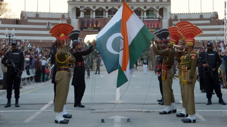 Pakistani Rangers and Indian Border Security Force personnel fold their respective national flags as they perform during the daily beating of the retreat ceremony on the India-Pakistan Border at Wagah on February 20, 2017.