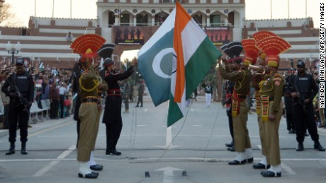Pakistani Rangers (REAR) and Indian Border Security Force (BSF) personnel fold their respective national flags as they perform during the daily beating of the retreat ceremony on the India-Pakistan Border at Wagah on February 20, 2017. / AFP / NARINDER NANU        (Photo credit should read NARINDER NANU/AFP/Getty Images)