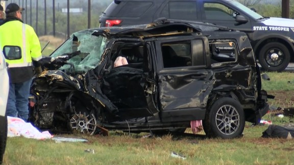 Authorities inspect one of two vehicles involved in a crash that killed three storm chasers in Texas.