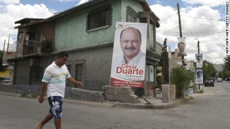 A man walks next to a poster with political propaganda of Chihuahua State Governor candidate, Cesar Duarte from the Institutional Revolutionary Party (PRI) on July 2, 2010, in Ciudad Juarez, Mexico. Sunday's elections in nearly half of Mexico's states are expected to serve as an unofficial referendum on President Felipe Calderon's clampdown on drug violence that is gripping the country.  AFP PHOTO/Jesus Alcazar (Photo credit should read Jesus Alcazar/AFP/Getty Images)
