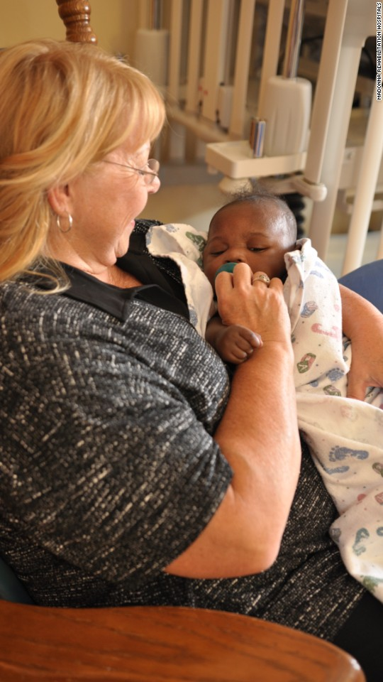 Carole Johnson comforts a baby at Madonna Rehabilitation Hospitals in Lincoln, Nebraska