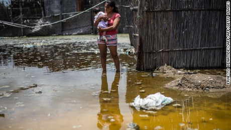 TOPSHOT - A woman and her baby stand in a flooded street, in the province of La Union in Piura, northern Peru, on March 25, 2017.  The El Nino climate phenomenon is causing muddy rivers to overflow along the entire Peruvian coast, isolating communities and neighbourhoods. / AFP PHOTO / Ernesto BENAVIDES        (Photo credit should read ERNESTO BENAVIDES/AFP/Getty Images)