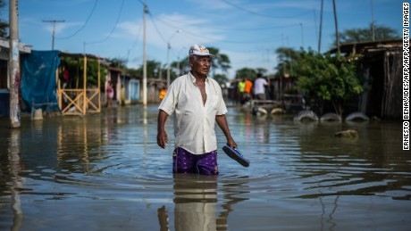 "A local resident wades through water on a street in the ""El Indio"" settlement on the outskirts of Piura, in northern Peru."