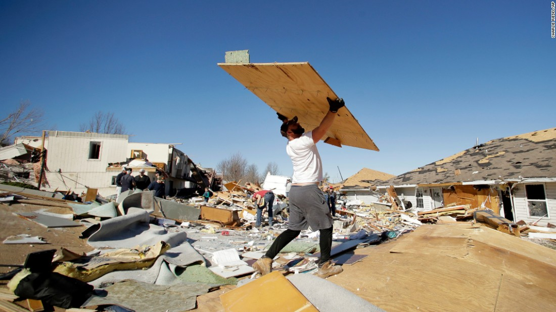 Bryant Carter removes debris as he helps salvages items from a friend's tornado-damaged home in Oak Grove, Missouri, on Tuesday, March 7.