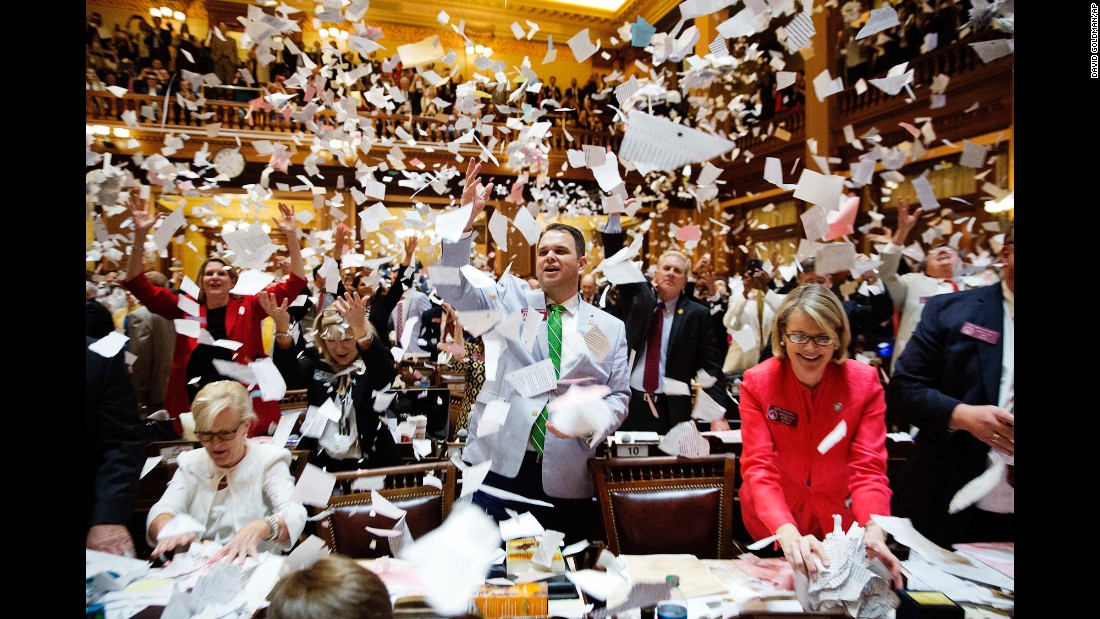 Georgia lawmakers throw paper into the air at the conclusion of the legislative session in Atlanta on Friday, March 31.