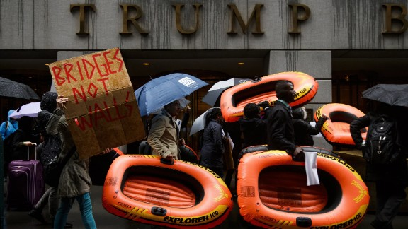 People carry inflatable rafts in front of New York's Trump Tower as they protest the President's refugee policies on Tuesday, March 28.