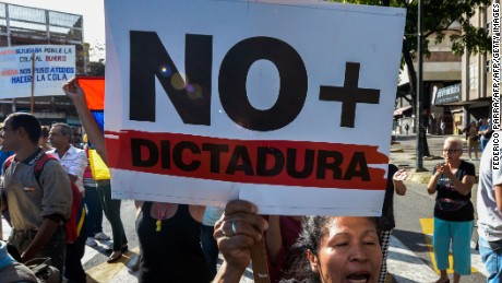 "A demonstrator in Caracas on Friday with sign reading ""No more dictatorship."""