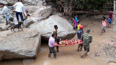 Soldiers and residents help evacuate one of the injured Saturday in Mocoa.
