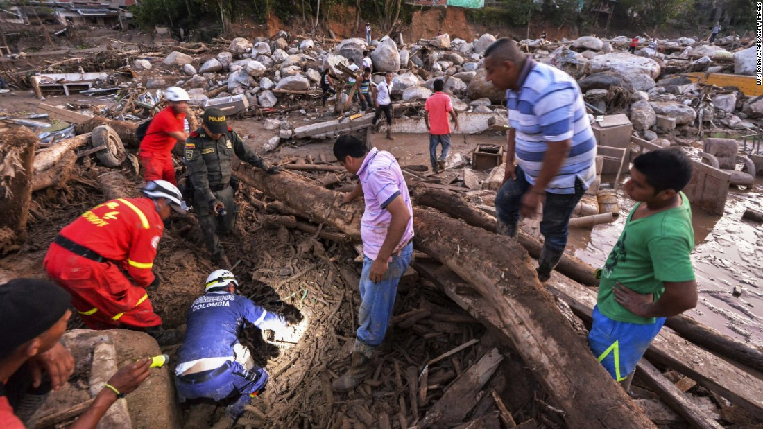 Rescuers search for people among the debris left by mudslides.