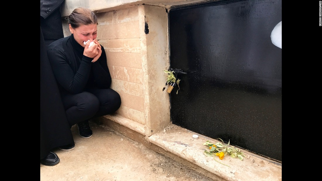 A Christian woman of Qaraqosh cries next to the tomb where Nasira was laid to rest.