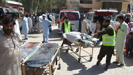 Pakistani volunteers transport the body of a victim following the attack at Ali Ahmad Gunnar Shrine.