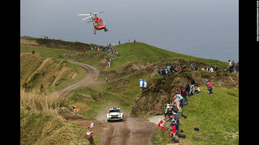 The rally car of Marijan Griebel and Stefan Kopczyk speeds past race fans in Ponta Delgada, Portugal, on Friday, March 31.