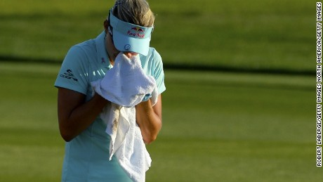Lexi Thompson cries in a towel as she walks to the 18th green after her second shot during the final round of the ANA Inspiration