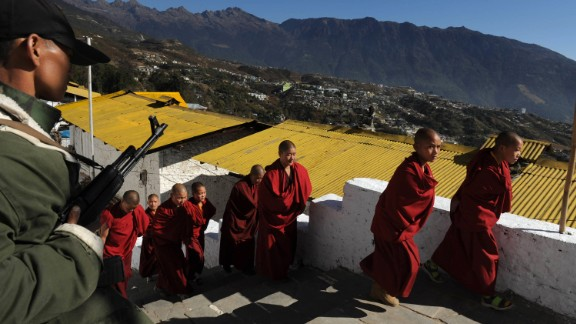 A security official, left, stands guard as monks arrive for the last visit by the Dalai Lama to Tawang Monastery in Arunachal Pradesh in November 2009.