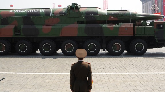 A North Korean soldier stands guard in front of a military vehicle carrying what is believed to be a Taepodong-class missile during a military parade to mark the 100th birthday of the country's founder Kim Il Sung in Pyongyang on April 15, 2012.
