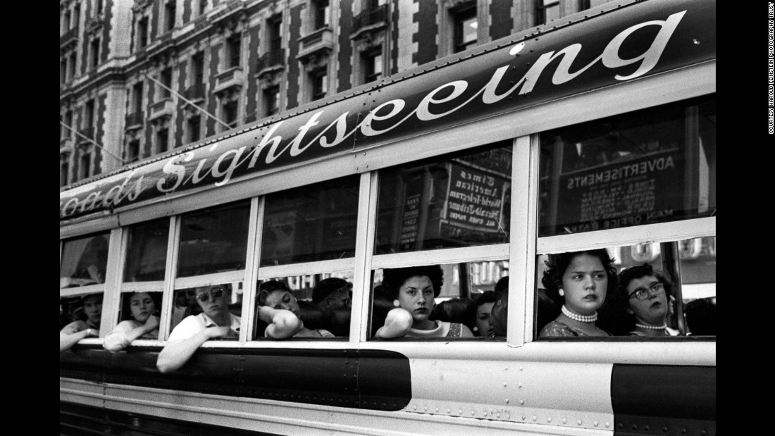 "Passengers look out of a sightseeing bus in New York in 1956. Bigaignon said Feinstein's street photography is characterized by a high sense of composition: ""He's the kind of photographer who took great care at composing his images in a very fine way, even though he was working very quickly. ... He was very much focused on composition, and that's probably one of the skills he had and he mastered better than the others."""
