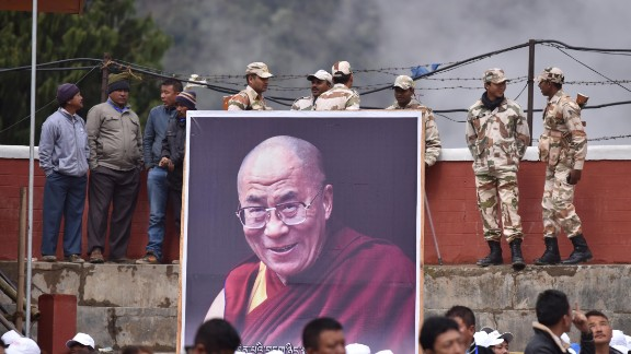 Indian security personnel stand with a poster of the Dalai Lama as he delivers religious teachings at the Buddha Stadium in Bomdila in India's northeastern state of Arunachal Pradesh state on April 5, 2017.