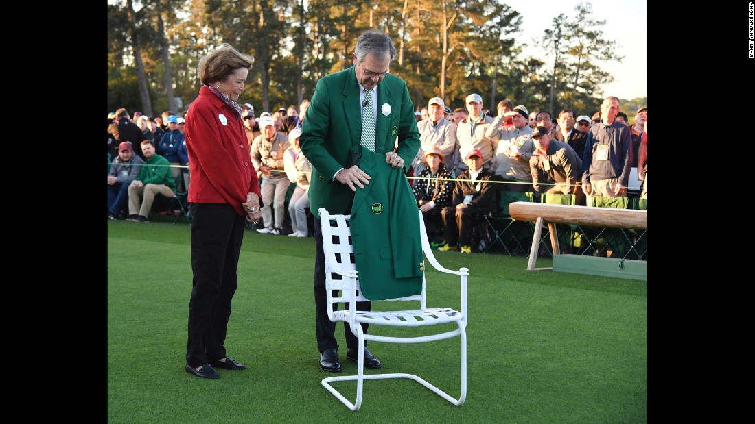 "Billy Payne, the chairman of the Augusta National Golf Club, places Arnold Palmer's jacket on a chair at the honorary start of the tournament. Palmer's wife, Kathleen, looks on. Palmer, a four-time Masters winner, <a href=""http://www.cnn.com/2016/09/25/us/arnold-palmer-death/index.html"" target=""_blank"">died in September</a> at the age of 87."
