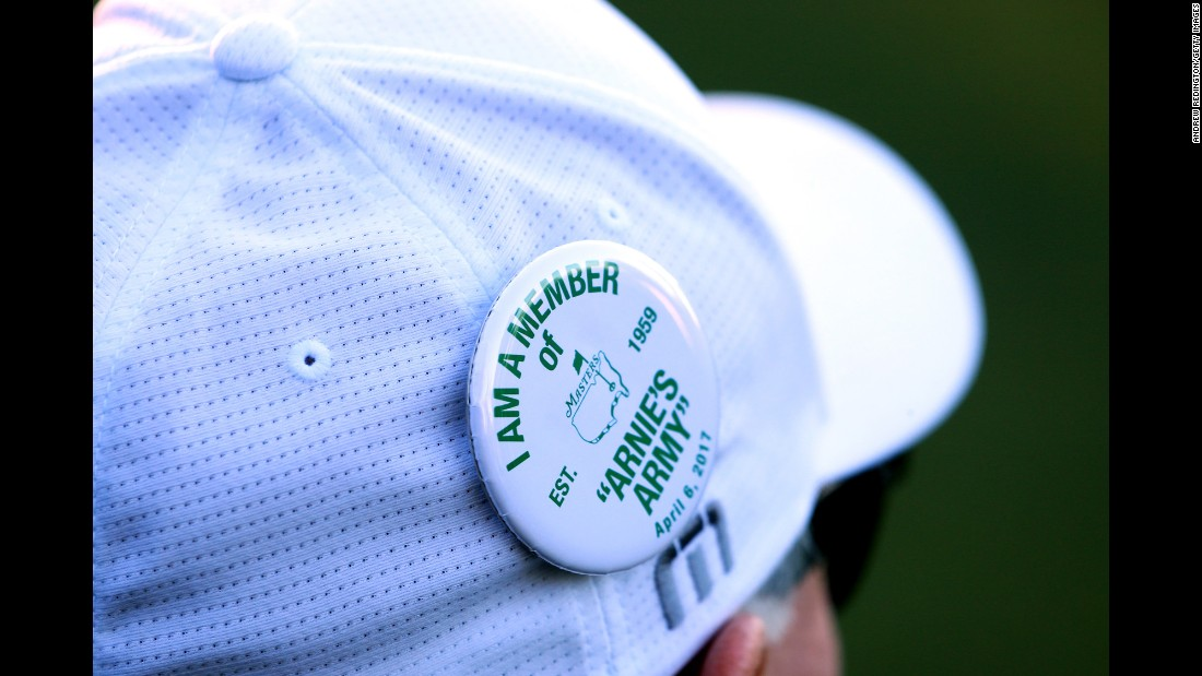 A fan wears a pin in honor of Arnold Palmer.