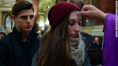 Local beleivers receive the ash-cross, given by father Attila Farkas (R) during a mass in the St Stephan Basilica at the beginning of Lent, which starts 40 days before Easter on February 10, 2016 during an evening mass for Ash Wednesday in Budapest, Hungary.   / AFP / ATTILA KISBENEDEK        (Photo credit should read ATTILA KISBENEDEK/AFP/Getty Images)
