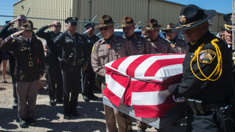 Officers from the Navajo Nation Police Department and the McKinley County Sheriff's Department carry the casket of fallen Navajo Nation Police Officer Houston Largo at Sunset Memorial Park in Gallup, N.M., Thursday, March 16, 2017. The 27-year-old decorated officer was shot while responding to a domestic violence call in remote New Mexico. (Cayla Nimmo/Gallup Independent via AP)