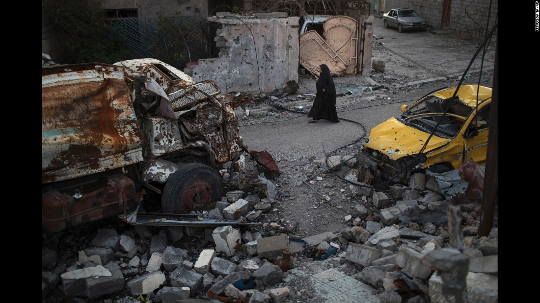 "A woman walks past damaged vehicles in Mosul, Iraq, on Wednesday, April 5. Iraqi forces <a href=""http://www.cnn.com/interactive/2017/03/world/mosul-iraq-cnnphotos/index.html"" target=""_blank"">have been fighting ISIS militants</a> for control of the city."