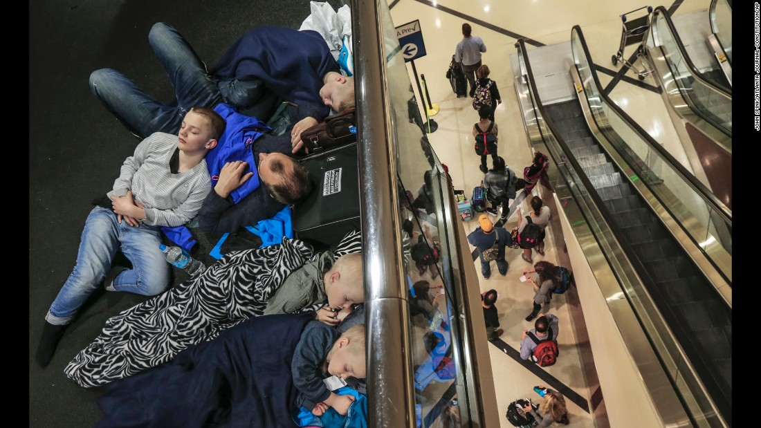 Stranded travelers rest at Atlanta's international airport on Thursday, April 6. Hundreds of flights were canceled because of severe thunderstorms in the area.