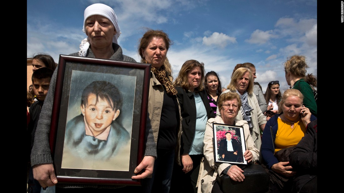 Sabrije Deliu, left, holds a portrait of her 6-year-old son Bleart during a ceremony in Rezalle, Kosovo, on Wednesday, April 5. Bleart was among those killed during the Kosovo War of 1998-99.