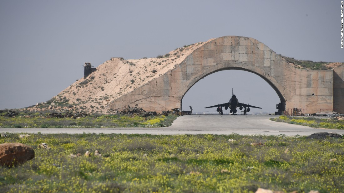 A plane is visible under an arch at the Shayrat airfield.