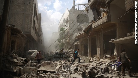 Syrians walk amid the rubble of destroyed buildings following reported air strikes by regime forces in the rebel-held area of Douma, east of the capital Damascus, on August 30, 2015. More than 240,000 people have been killed since Syria's conflict began in March 2011, and half of the country's population has been displaced by the war. AFP PHOTO / ABD DOUMANY / AFP / ABD DOUMANY        (Photo credit should read ABD DOUMANY/AFP/Getty Images)