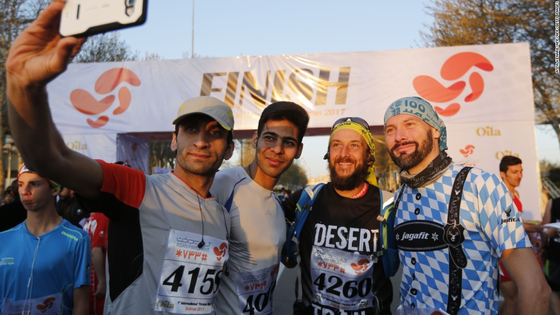 Foreigners and locals pose for pictures at the finish line.