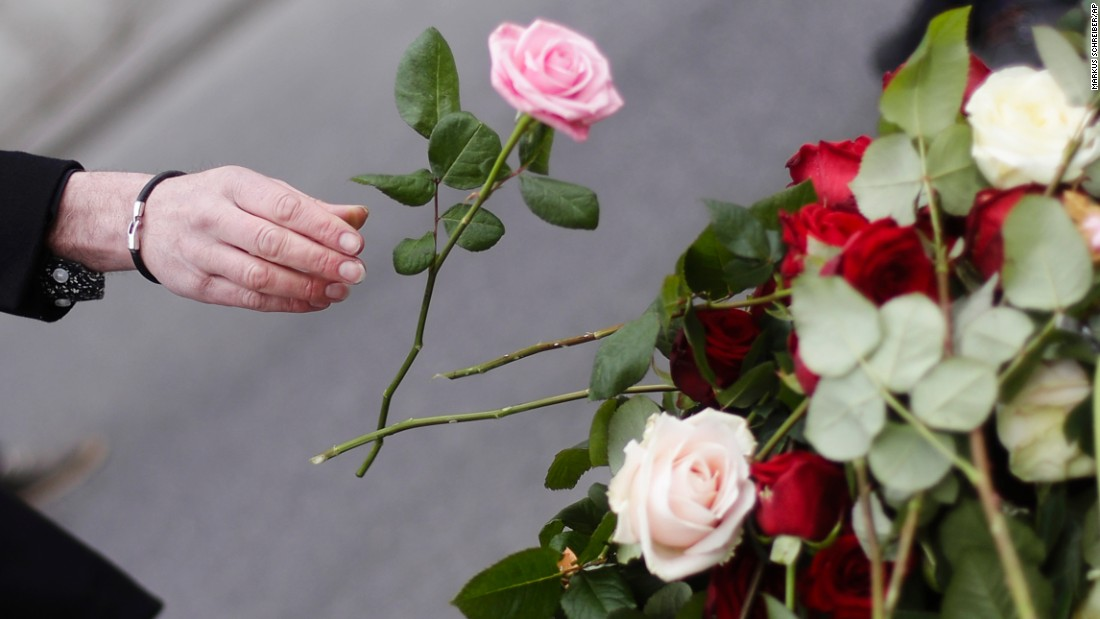A woman tosses a flower onto the memorial in central Stockholm.