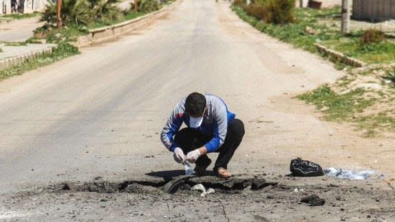 A Syrian man collects samples from the site of a suspected chemical attack in Khan Sheikhoun, in Syria's northwestern Idlib province, on April 5.