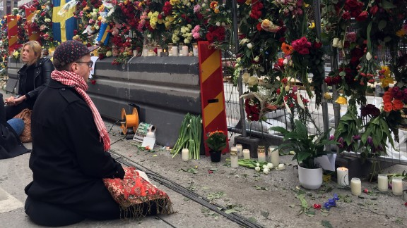 A mourner prays at a memorial near the site of the Stockholm attack.