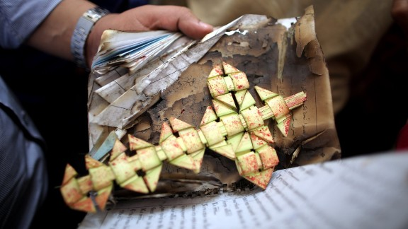 A member of the security forces carries a palm leaf at the scene of a bomb explosion inside Mar Girgis church in Tanta, Egypt.
