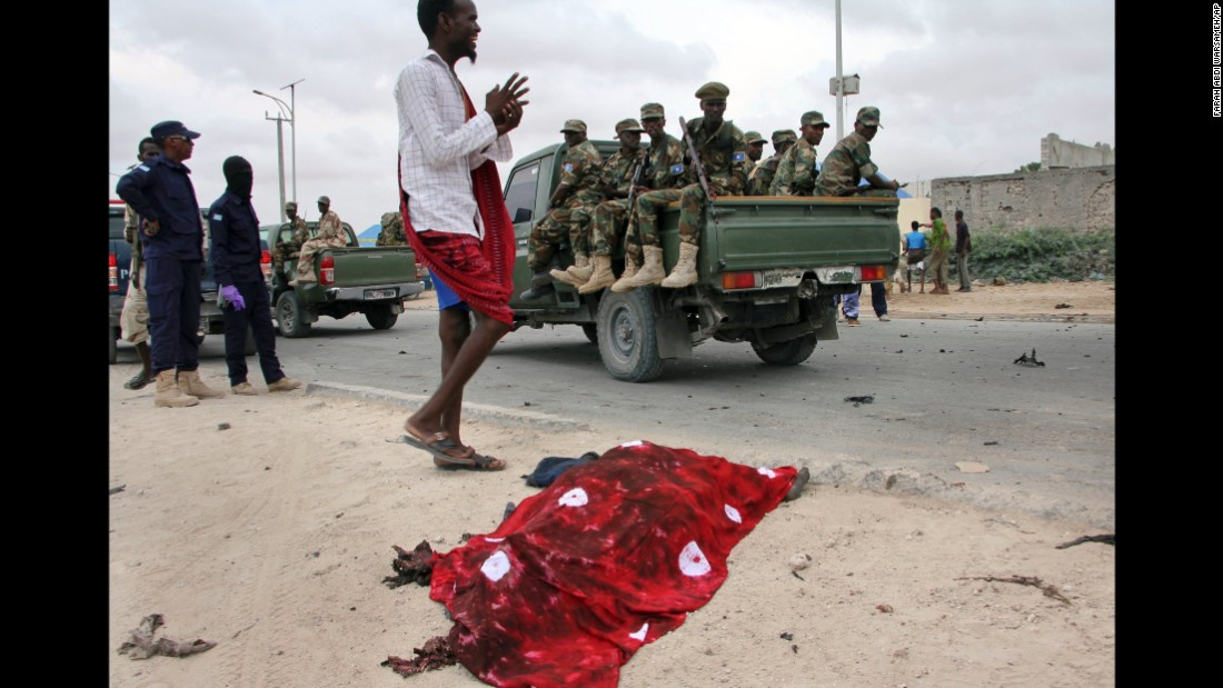 Soldiers in a truck pass by the covered body of a bomb attack victim.