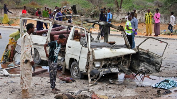 A Somali soldier stands by the wreckage of a minibus that was destroyed by the car bomb.