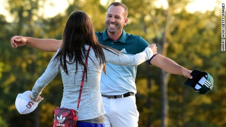 Sergio Garcia of Spain embraces fiancee Angela Akins after defeating Justin Rose