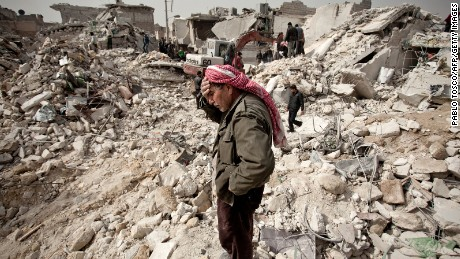 A Syrian man reacts while standing on the rubble of his house while others look for survivors and bodies in the Tariq al-Bab district of the northern city of Aleppo on February 23, 2013. Three surface-to-surface missiles fired by Syrian regime forces in Aleppo's Tariq al-Bab district have left 58 people dead, among them 36 children, the Syrian Observatory for Human Rights said on February 24. AFP PHOTO/PABLO TOSCO        (Photo credit should read Pablo Tosco/AFP/Getty Images)