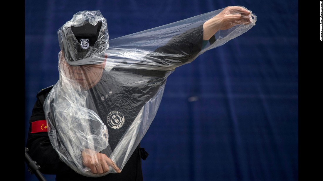 A security officer puts on a rain poncho Thursday, April 6, as he works at the site of the Formula One race in Shanghai, China.
