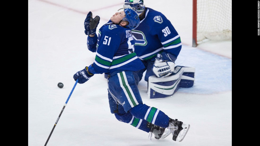 Vancouver's Troy Stecher reacts after getting hit in the face by a puck during an NHL game on Saturday, April 8.