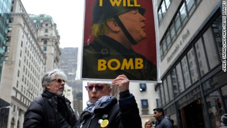 An anti-war protester displays a placard against US President Donald Trump during a demonstration in front of the Trump Tower in New York on April 7, 2017, to protest the US air strike in Syria.   The United States on April 7 warned it was ready to hit Syria again after targeting an air base in a strike that infuriated Moscow and fueled calls for a new diplomatic push to end the six-year war.   / AFP PHOTO / Jewel SAMAD        (Photo credit should read JEWEL SAMAD/AFP/Getty Images)