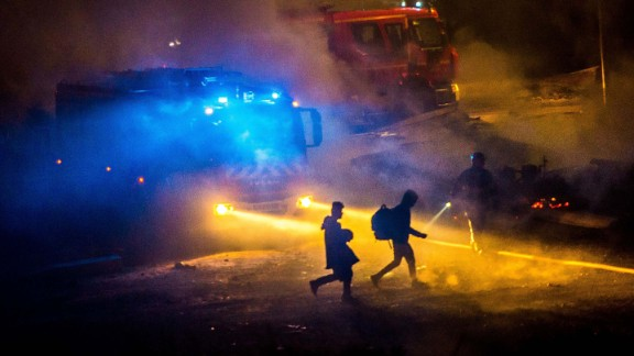 Migrants flee the blaze that reduced the Grande-Synthe camp to ashes.