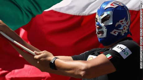 An F1 fan waves a Mexican flag while wearing a lucha libre mask
