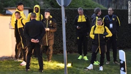 Head coach Thomas Tuchel, far right, and Borussia Dortmund players stand outside their team bus.