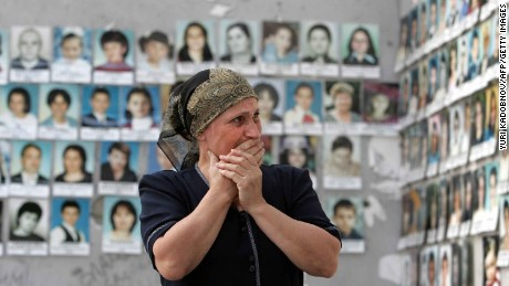 A woman cries as she looks at the pictures of children killed in the school sports hall in Beslan, 30 August 2005.