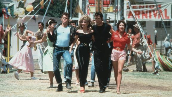 Jeff Conaway, Olivia Newton-John, John Travolta and Stockard Channing walk arm in arm at a carnival in a still from the film,