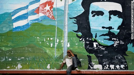 "A Cuban rests next to a graffiti depicting Argentine-Cuban revolutionary Ernesto ""Che"" Guevara, in Havana"