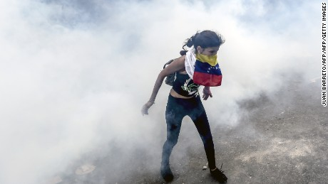 Venezuelan opposition activists react to tear gas shot by the police during protests against the government of President Nicolas Maduro on April 6, 2017 in Caracas. The center-right opposition vowed fresh street protests - after earlier unrest left dozens of people injured - to increase pressure on Maduro, whom they blame for the country's economic crisis. / AFP PHOTO / JUAN BARRETO        (Photo credit should read JUAN BARRETO/AFP/Getty Images)